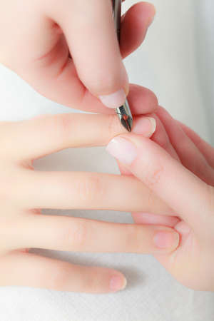 Close up of hands. Beautician trimming cuticles of female client. Manicure and skincare. Woman in spa beauty salon. photo