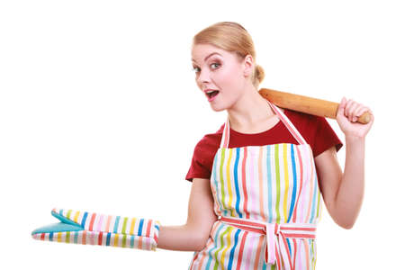 Happy housewife or baker chef wearing kitchen apron oven mitten holds baking rolling pin showing empty copy space presenting with open hand palm isolated on white photo
