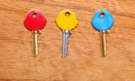 house coats: Three house keys with colorful plastic coats caps on wooden table .