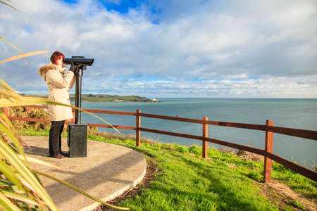 woman looking through sightseeing binoculars tourist telescope overlooking the ocean landscape, Church Bay Ireland Europe photo