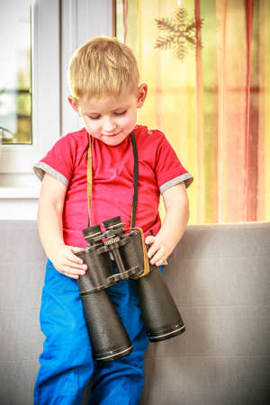 Happy childhood  Portrait of boy child kid preschooler playing with binoculars  At home  Real  photo