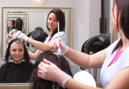 Reflection in mirror  Brunette woman in hairdressing beauty salon  Girl dying hair by hairstylist  hairdresser colouring client hair  photo