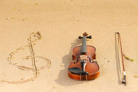 Violin string and g treble clef shape on sandy beach. Love of music concept