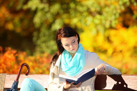 Fall lifestyle concept  Casual young woman girl relaxing in autumnal park reading book  Golden colorful leaves  photo