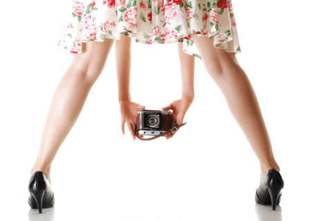 womans legs and hand girl taking picture using vintage camera white background photo