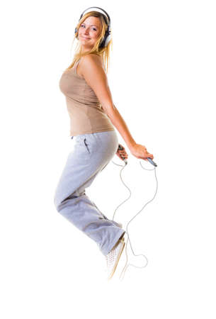 Sport girl plus size doing exercise with skip jump rope - weight loss  Fitness young woman with headphones listening to music isolated  Studio shot  photo