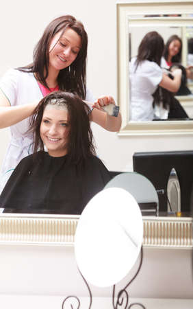 Brunette woman in hairdressing beauty salon  Girl dying hair by hairstylist  hairdresser colouring client hair  photo