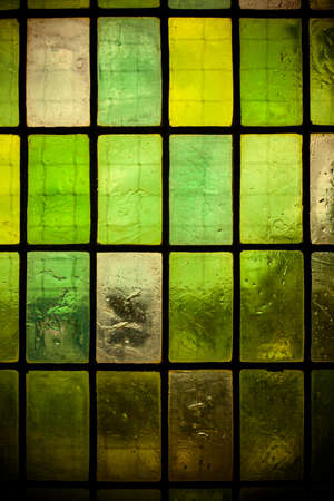 multicolored stained glass window with regular block pattern in hue of green photo