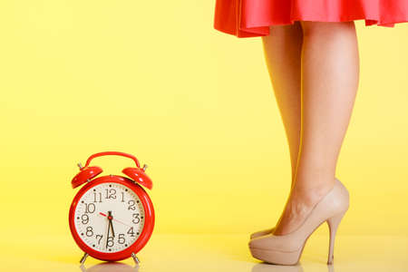 f�minit�: Les jambes des femmes sexy en hauts talons beiges debout � c�t� de l'horloge rouge sur fond jaune. Temps pour la f�minit�. Studio photo. Banque d'images