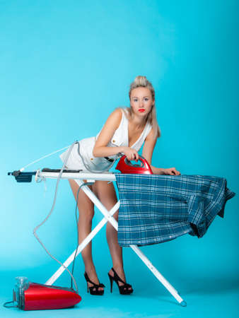 Full length sexy girl retro style ironing male shirt, woman housewife in domestic role. Traditional sharing household chores.  Pin up housework.   photo