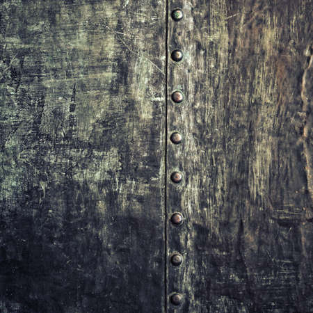 Closeup of grunge black metal plate with rivets and screws as texture. Square format. photo