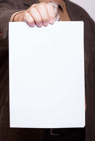 Business concept  Businessman holding empty poster sheet of paper, copy space for text  Male hands with blank advertisement card  photo