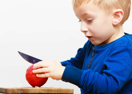 Blond boy child kid preschooler with kitchen knife cutting fruit apple at home  Childhood   photo