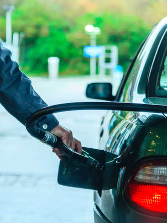 Male hand refilling the car with gas or petrol on filling station, holding a fuel pump outdoor photo