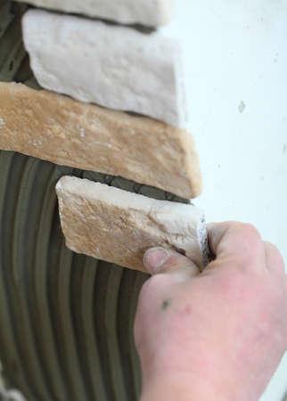 clinker tile: Renovaci�n a los trabajadores a domicilio de instalar baldosas de clinker en un sitio de construcci�n de la pared