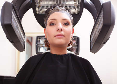 Brunette young woman in hairdressing beauty salon. Girl dying colouring hair by hairstylist hairdresser. Modern professional equipment. photo