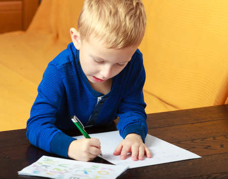 Happy childhood  Blond boy child kid with pen writing on piece of paper doing homework  At home  photo