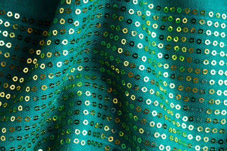 Green shiny sequine background texture abstract cloth wavy folds. Elegant sequined sparkling textile close up photo