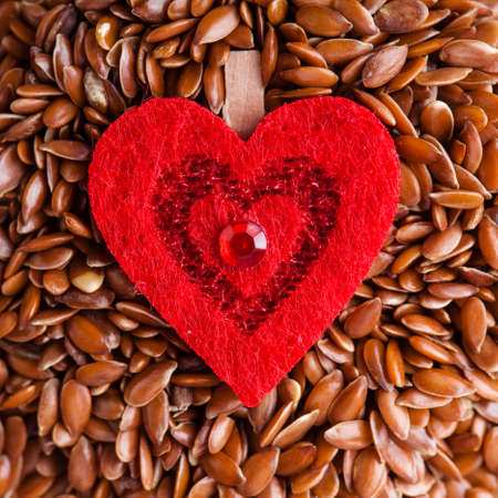 diet healthcare concept. Brown raw flax seeds linseed and red heart symbol. Healthy food  for preventing heart diseases. Flaxseeds are full of omega-3 fatty acids. photo
