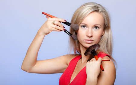visagiste: Portrait of blond girl holding professional makeup brushes on violet. Young woman as visagiste or stylist. Studio shot.