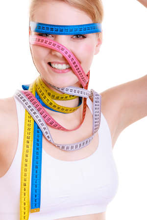 obsessed: Time for diet slimming weight loss concept. Health care healthy lifestyle. Sport fit fitness woman with a lot of colorful measure tapes around her head. Obsessed girl by your body.  isolated on white background Stock Photo
