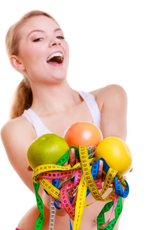 Time for diet slimming weight loss. Health care healthy lifestyle. Happy sport fit fitness woman blonde girl with a lot of colorful measure tapes and fruits isolated on white background