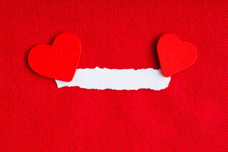 Piece scrap of white paper blank copy space and hearts symbols of love on red fabric textile material background. Valentines day. photo