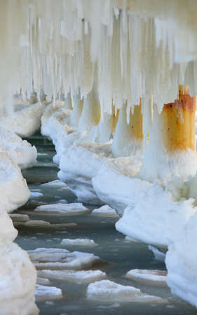 Winter scenery. Close up detail of old pier in Gdynia Orlowo Poland with ice formations icicles. Frozen Sea Baltic covered with snow, seasonal specific. photo