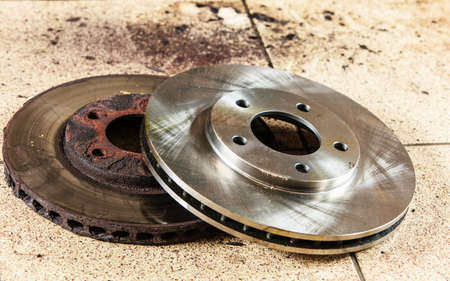 Auto in service. New and old front brake disks for modern car lying on floor in mechanic garage car service. photo