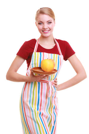 Happy housewife or chef in colorful kitchen offering red yellow apple healthy fruit isolated studio shot  Diet and nutrition   photo