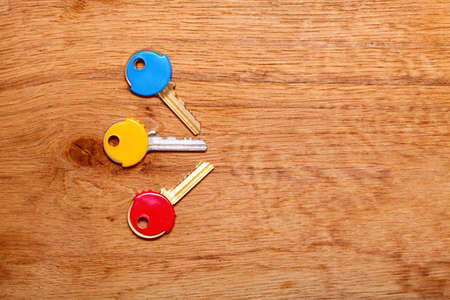 house coats: Three house keys with colorful plastic coats caps on wooden table background  Copy space for text