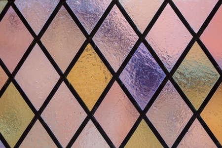 背景ピンク紫音として多着色されたダイヤモンド パターンを持つステンド グラス