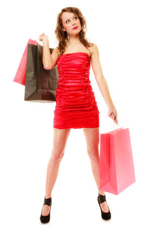 Full length of elegant girl young woman in red dress with paper shopping bags isolated on white. Sale and retail. Studio shot. photo