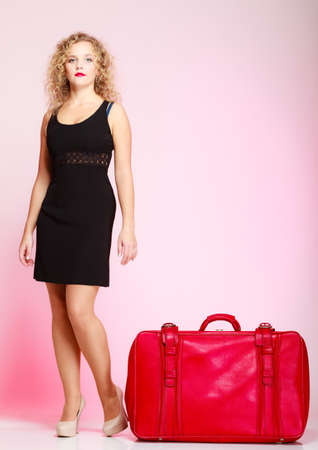 Full length of young elegant lady in voyage, traveler woman with old red suitcase luggage bag on pink background. Travel theme photo
