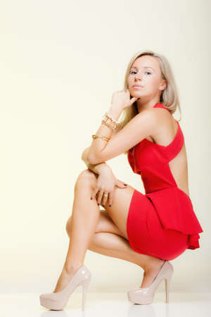 Fashion woman in full length. Girl in fashionable red dress posing. Studio shot yellow background photo