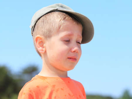 Sad child. Portrait of crying unhappy little boy outdoor photo