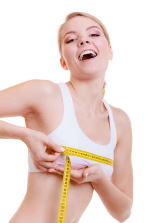 Fitness girl sporty smiling woman measuring her bust size chest with measurement tape isolated on white background photo