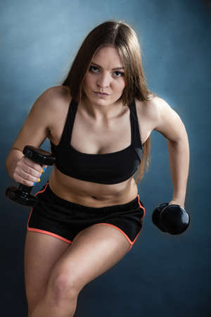dumb bells: Fitness girl fit woman lifting dumbbells weights doing exercise with dumb bells training shoulder muscles dark blue background
