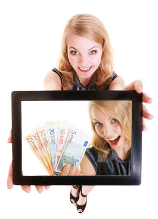 welth: Happy smiling blond businesswoman showing touchpad with photo of euro money. Modern young woman girl holding tablet touchpad and dreaming about be rich.