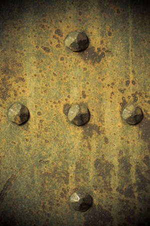 Brown grunge metal plate or armour texture with rivets as background photo
