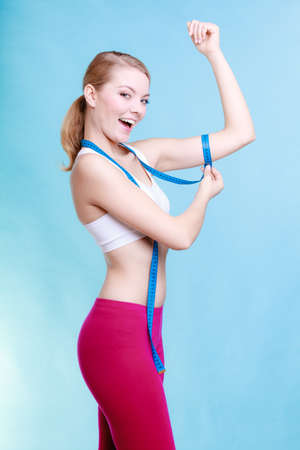 Fitness girl sporty smiling woman measuring her biceps with measurement tape on blue background photo