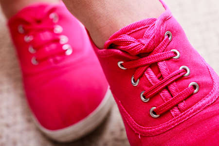 shoestrings: Closeup of casual vibrant pink sneakers plimsolls shoes boots on female feet  Sport fashion