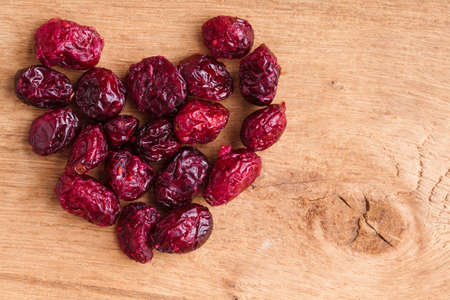 cranberry fruit: Healthy food organic nutrition. Heap of dried cranberries cranberry fruit on wooden table background