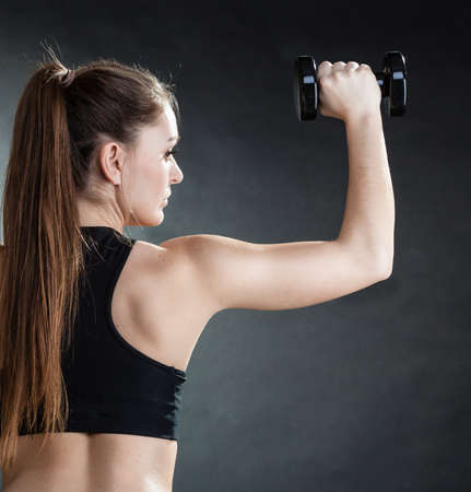 Fitness girl fit woman lifting dumbbells weights doing exercise with dumb bells training shoulder muscles back view gray background