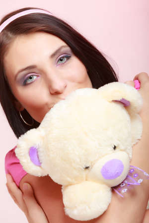 longing: Portrait of childish young woman with headband holding toy. Infantile girl hugging kissing teddy bear on pink. Longing for childhood. Studio shot. Stock Photo