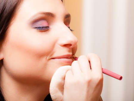 visagiste: Female beauty. Makeup artist applying with pink pencil cosmetic on lips of her client young woman. Girl by visagiste.