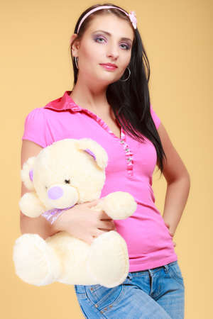 longing: Portrait of childish young woman with headband holding toy. Infantile girl in pink hugging teddy bear on orange. Longing for childhood. Studio shot.
