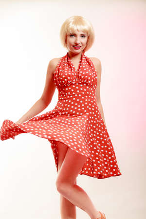 Vintage pinup style. Beautiful stylized young woman dancing. Attractive girl in blond wig and retro spotted red dress on pink. Disguise. Party. Studio shot. photo