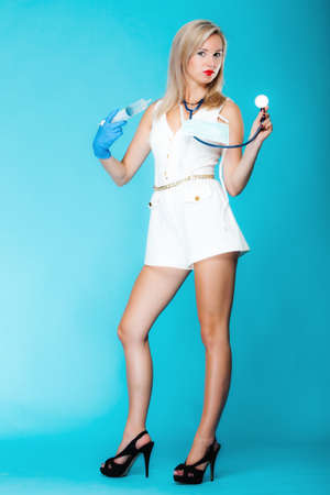 Full length funny sexy girl doctor nurse with syringe stethoscope. Medical person for health insurance. Vivid blue background Stock Photo