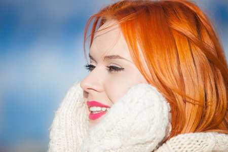Portrait winter fashion beautiful woman red haired girl in warm clothing pink lips outdoor blue sky background photo